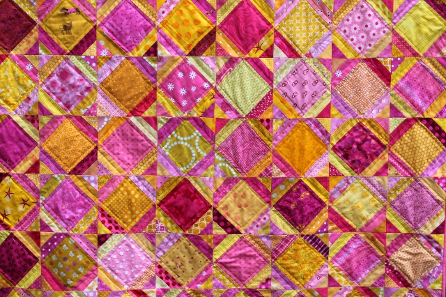 Bright easy kids quilt made with pink and yellow fabric.